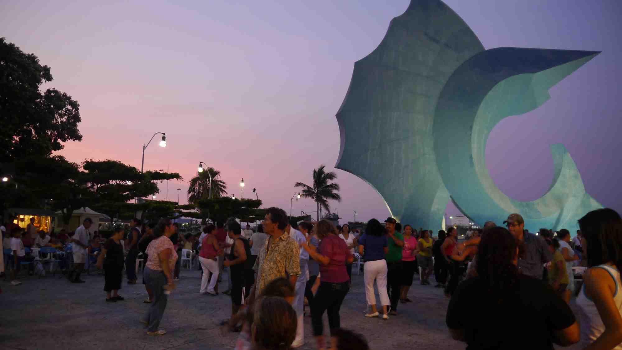 personas bailando cerca del pez vela de manzanillo